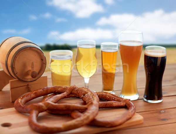 beer glasses, barrel and pretzel over cereal field Stock photo © dolgachov
