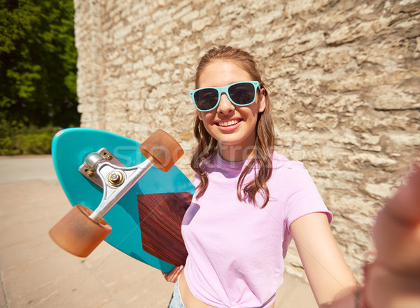 teenage girl with longboard taking selfie outdoors Stock photo © dolgachov
