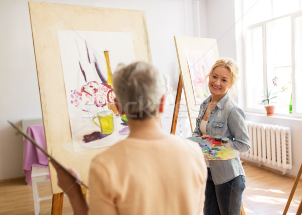 artist women with easels painting at art school Stock photo © dolgachov
