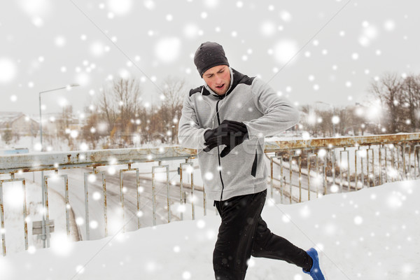 man with earphones running along winter bridge Stock photo © dolgachov