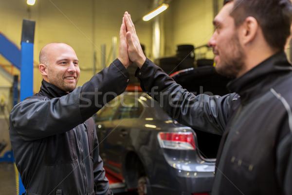 auto mechanics making high five at car shop Stock photo © dolgachov