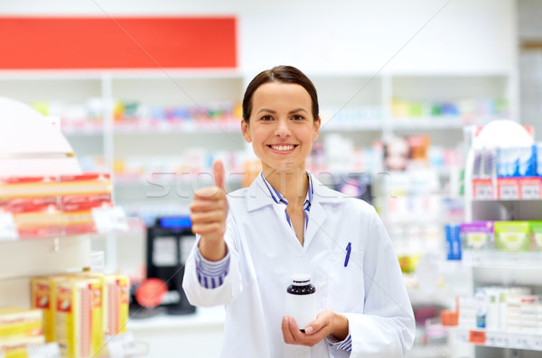apothecary with drug showing thumbs up at pharmacy Stock photo © dolgachov