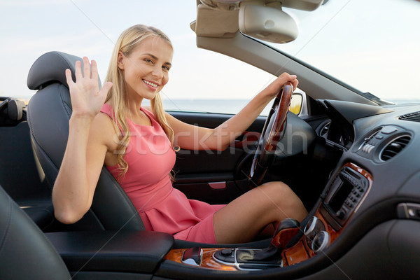 Stock photo: happy young woman in convertible car waving hand