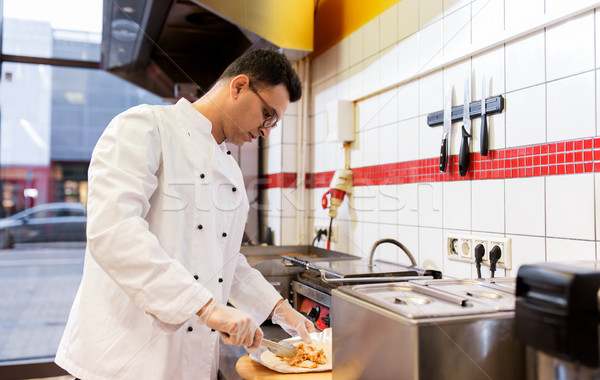 chef making shawarma wrap with meat at kebab shop Stock photo © dolgachov
