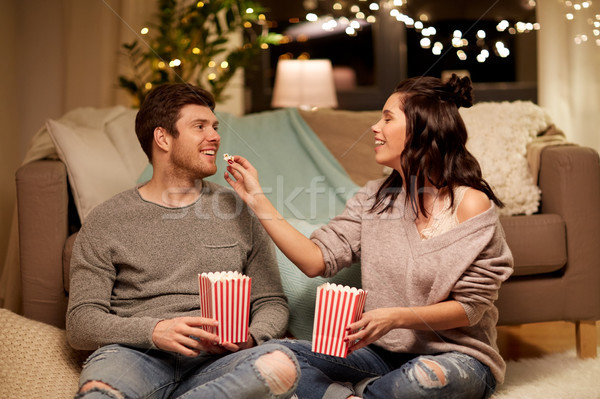 happy couple eating popcorn at home Stock photo © dolgachov