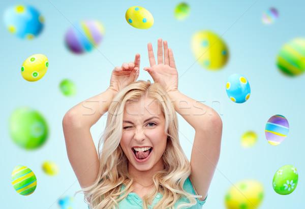 Heureux femme lapin oreilles œufs de Pâques Photo stock © dolgachov