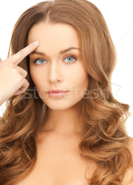 Stock photo: beautiful woman pointing at her forehead