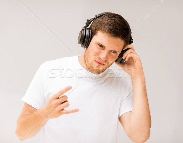 man with headphones listening rock music Stock photo © dolgachov