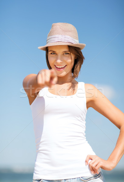girl in hat pointing at you on the beach Stock photo © dolgachov