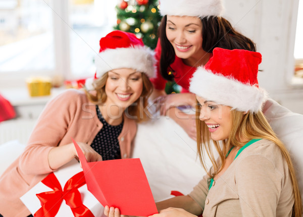 women in santa helper hats with card and gifts Stock photo © dolgachov