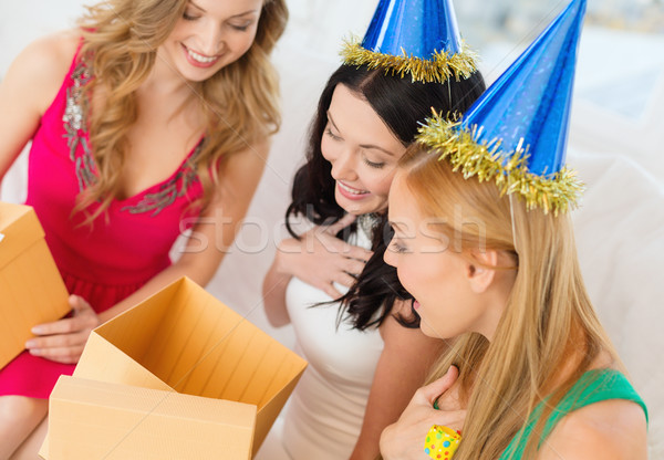 three smiling women in blue hats with gift boxes Stock photo © dolgachov