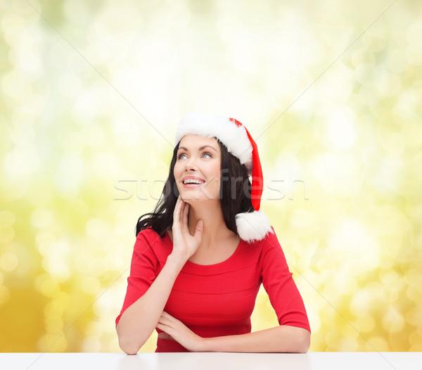 surprised woman in santa helper hat looking up Stock photo © dolgachov