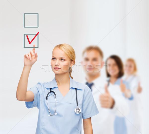 smiling doctor or nurse pointing to checkmark Stock photo © dolgachov