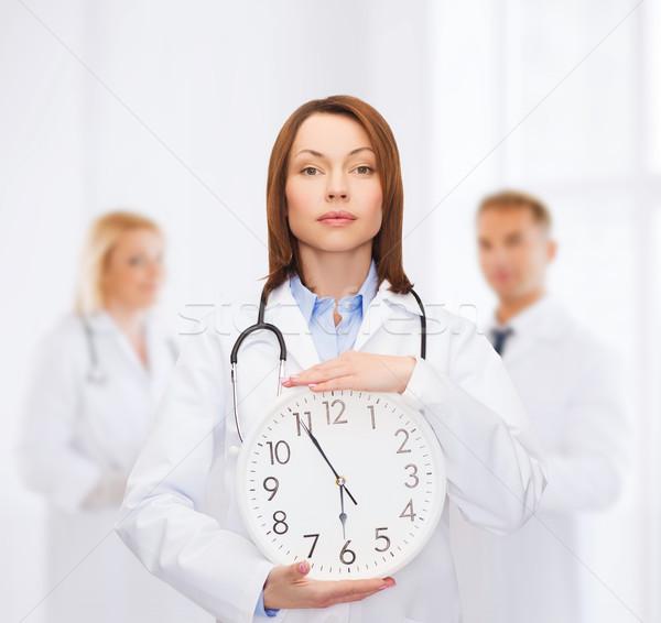 calm female doctor with wall clock Stock photo © dolgachov