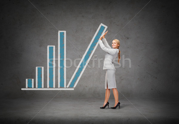 young smiling businesswoman pushing up chart bar Stock photo © dolgachov