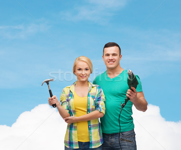 smiling couple with hammer and drill Stock photo © dolgachov