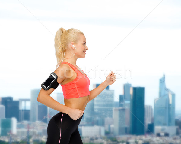 sporty woman running with smartphone and earphones Stock photo © dolgachov