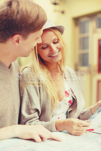 couple with map, camera and city guide in cafe Stock photo © dolgachov