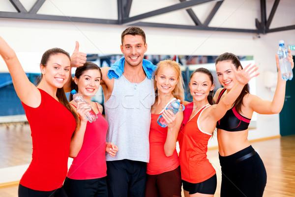 Grupo pessoas felizes ginásio água garrafas fitness Foto stock © dolgachov