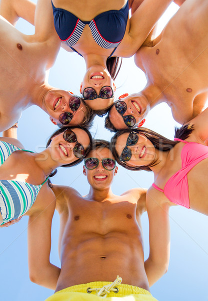 smiling friends in circle on summer beach Stock photo © dolgachov