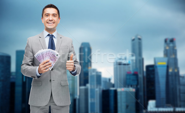 smiling businessman with money showing thumbs up Stock photo © dolgachov