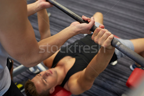 two young men with barbell flexing muscles in gym Stock photo © dolgachov