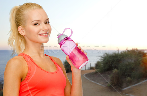 happy woman drinking water from bottle outdoors Stock photo © dolgachov