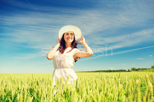 Stock photo: smiling young woman in straw hat on cereal field