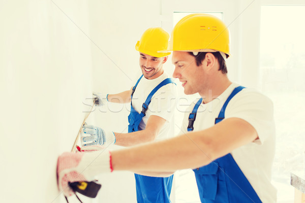 smiling builders with measuring tape indoors Stock photo © dolgachov