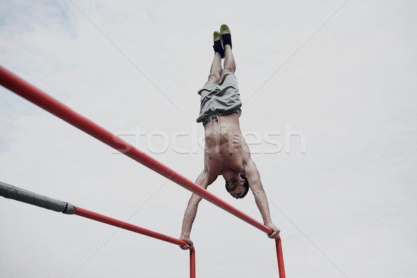 Jonge man parallel bars buitenshuis fitness Stockfoto © dolgachov