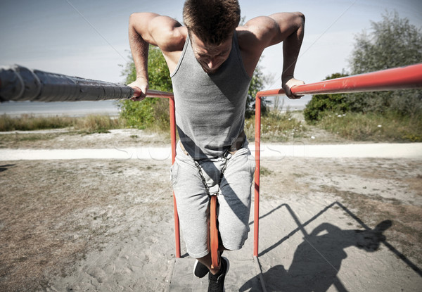 Jeune homme parallèle bars extérieur fitness Photo stock © dolgachov