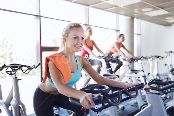 group of women riding on exercise bike in gym Stock photo © dolgachov