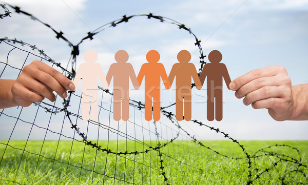 Stock photo: hands holding people pictogram over barb wire