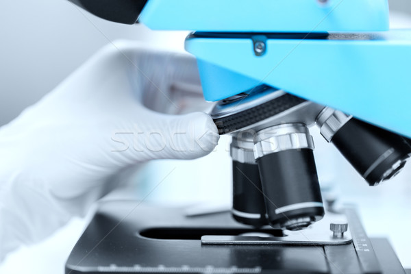 close up of scientist hand setting microscope Stock photo © dolgachov
