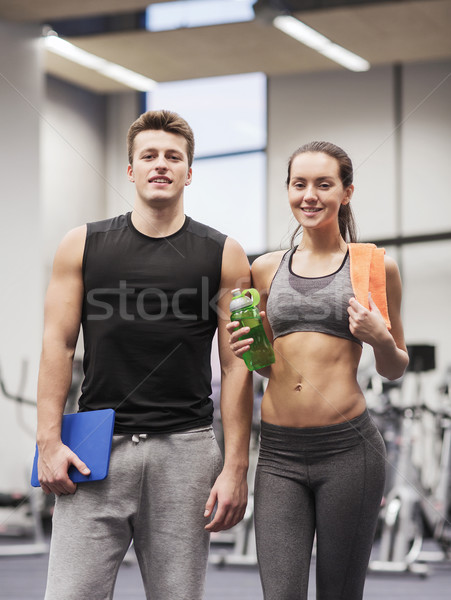 happy couple in gym with water and tablet pc Stock photo © dolgachov