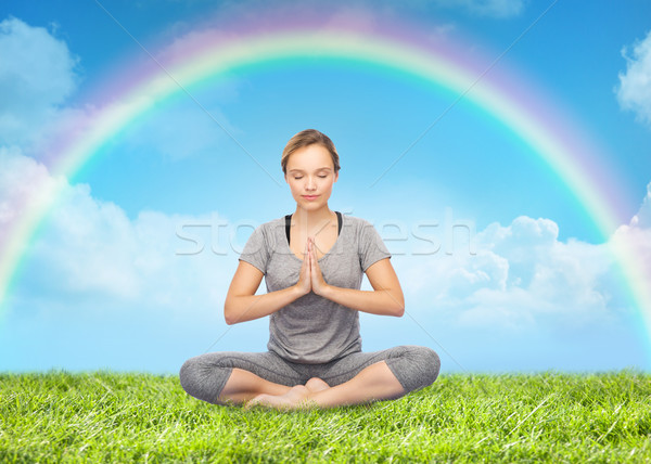 woman meditating in lotus yoga pose over rainbow  Stock photo © dolgachov