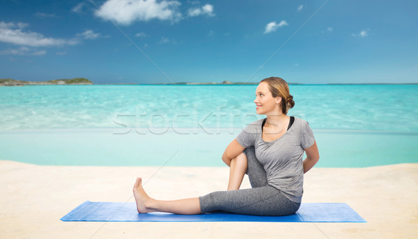 woman making yoga in twist pose on mat over beach  Stock photo © dolgachov