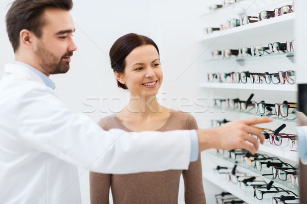 woman with glasses and optician at optics store Stock photo © dolgachov