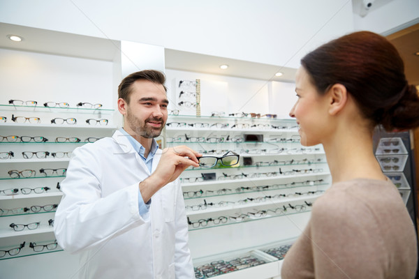optician giving glasses to woman at optics store Stock photo © dolgachov