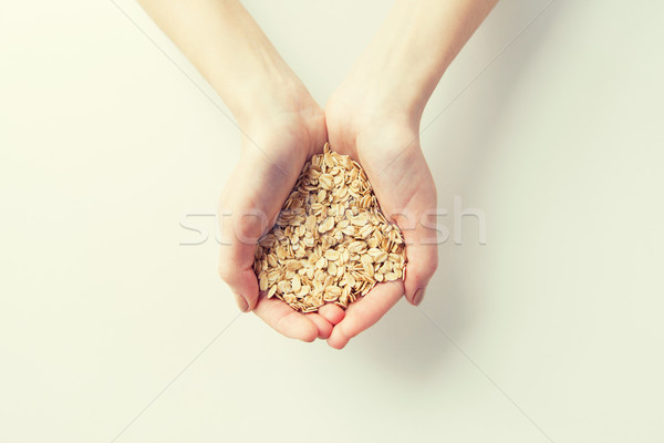 close up of woman hands holding oatmeal flakes Stock photo © dolgachov