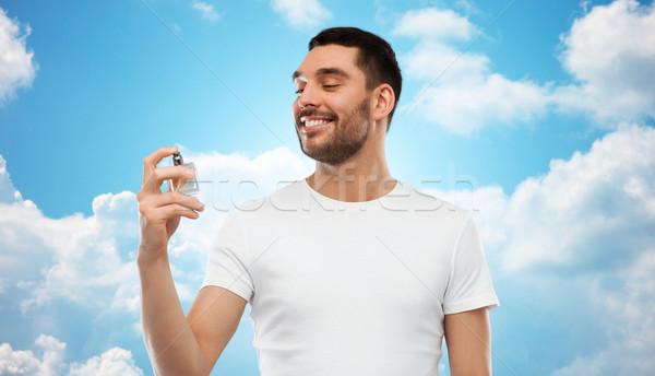 Souriant homme Homme parfum ciel bleu parfumerie Photo stock © dolgachov