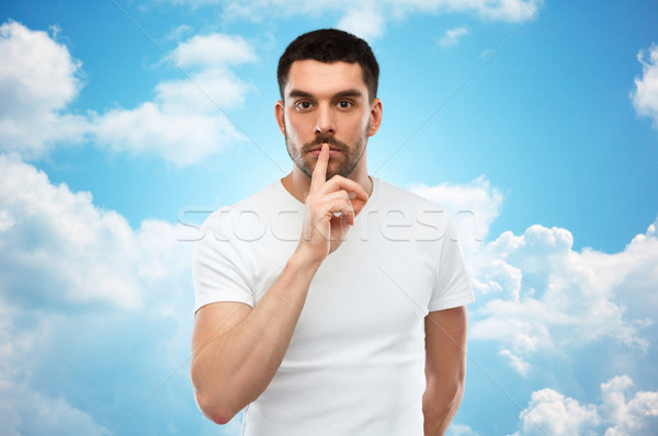 young man making hush sign over blue sky Stock photo © dolgachov