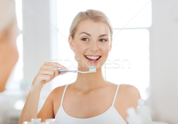 woman with toothbrush cleaning teeth at bathroom Stock photo © dolgachov
