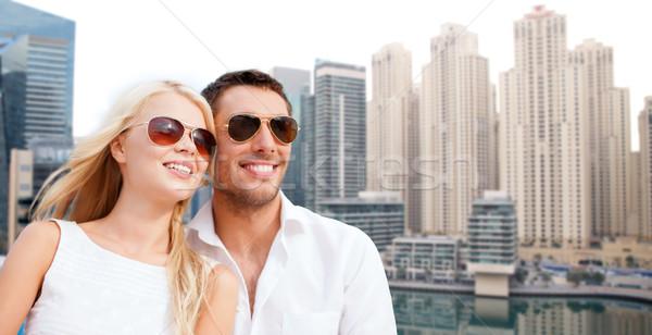 happy couple in shades over dubai city background Stock photo © dolgachov