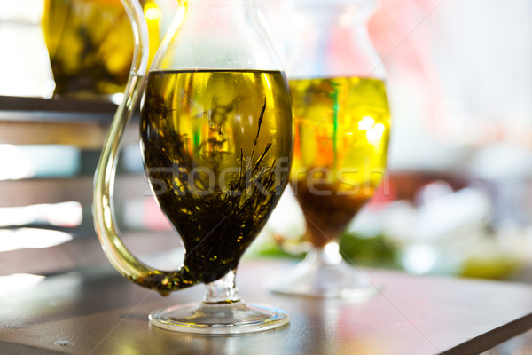 close up of glass jug with extra vergin olive oil Stock photo © dolgachov