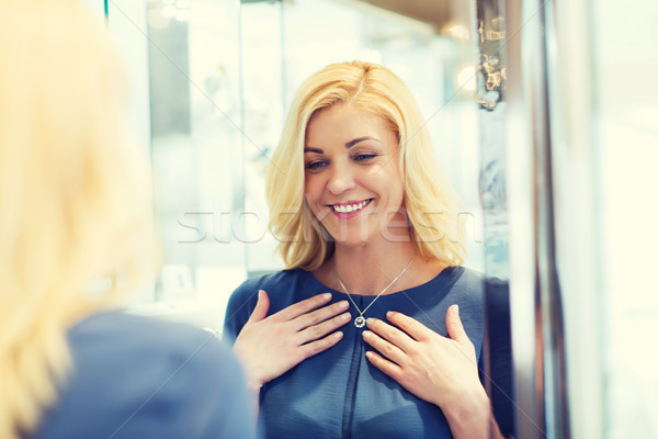 happy woman choosing pendant at jewelry store Stock photo © dolgachov