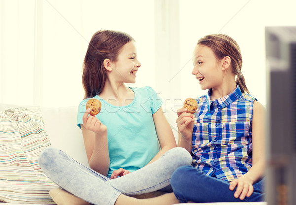 happy girls watching tv and eating cookies at home Stock photo © dolgachov