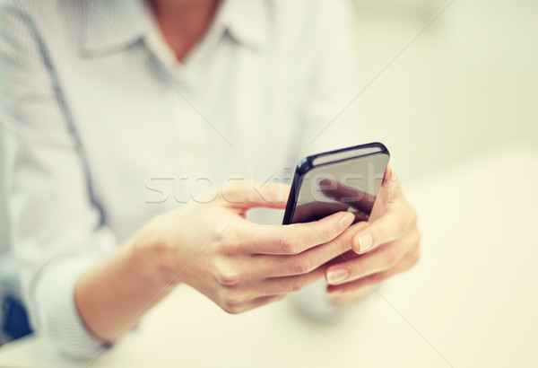 close up of woman texting on smartphone at office Stock photo © dolgachov