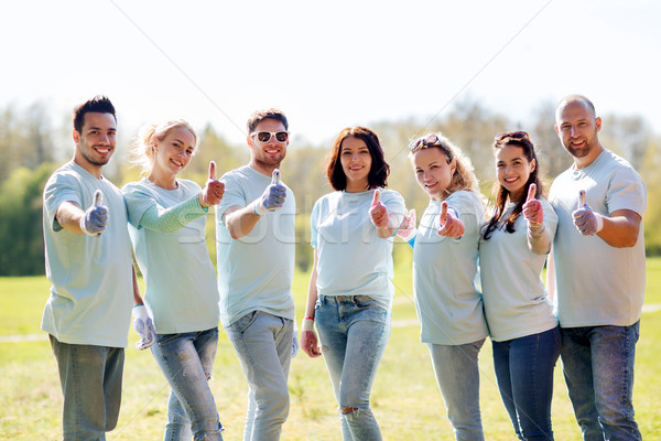 group of volunteers showing thumbs up in park Stock photo © dolgachov