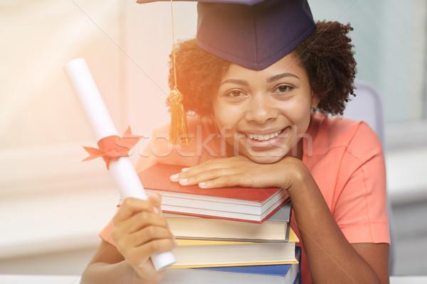 Gelukkig afrikaanse vrijgezel meisje boeken diploma Stockfoto © dolgachov